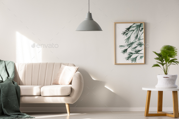 Real photo of a couch with blanket and pillow standing next to a - Stock Photo - Images