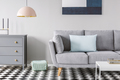 Pink lamp above grey cabinet next to sofa on checkered floor in - PhotoDune Item for Sale