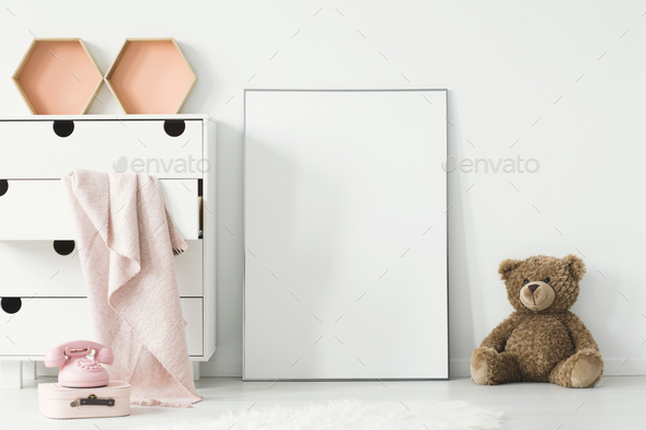 Teddy bear next to white empty poster in baby's room interior wi - Stock Photo - Images