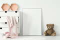 Teddy bear next to white empty poster in baby's room interior wi - PhotoDune Item for Sale