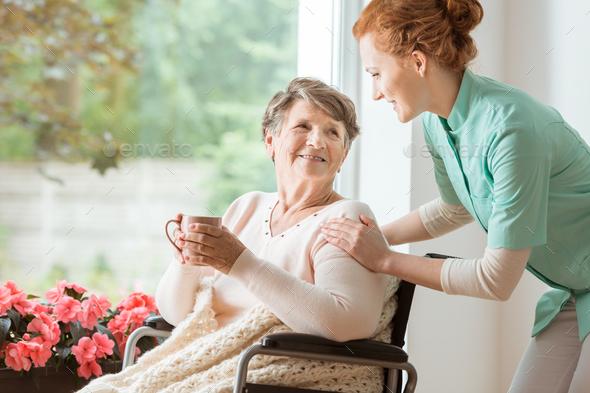 A professional caretaker in uniform helping a geriatric female p - Stock Photo - Images