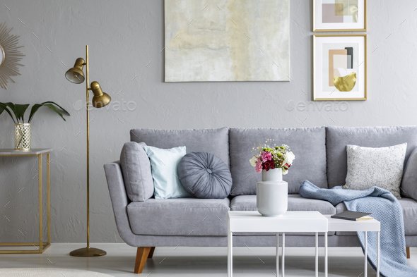Gold lamp next to grey sofa in modern living room interior with - Stock Photo - Images