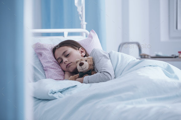 Sick girl sleeping with teddy bear in the hospital - Stock Photo - Images