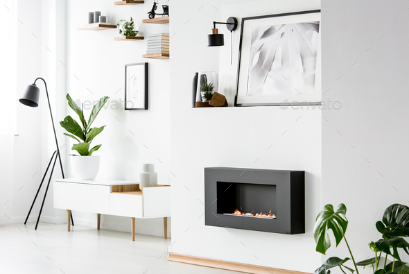Poster above black fireplace in white apartment interior with pl - Stock Photo - Images