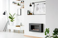 Poster above black fireplace in white apartment interior with pl - PhotoDune Item for Sale