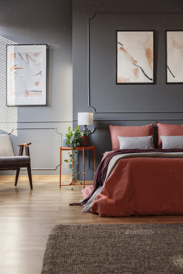 Orange bed against dark wall with molding and white posters next - Stock Photo - Images