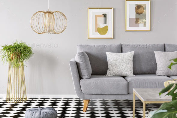 Real photo of a living room interior with gold posters on the wa - Stock Photo - Images