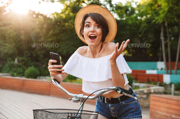 Joyful young girl in summer clothes riding bicycle - Stock Photo - Images