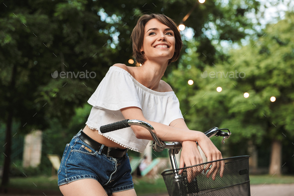 Smiling young girl in summer clothes sitting on a bicycle - Stock Photo - Images