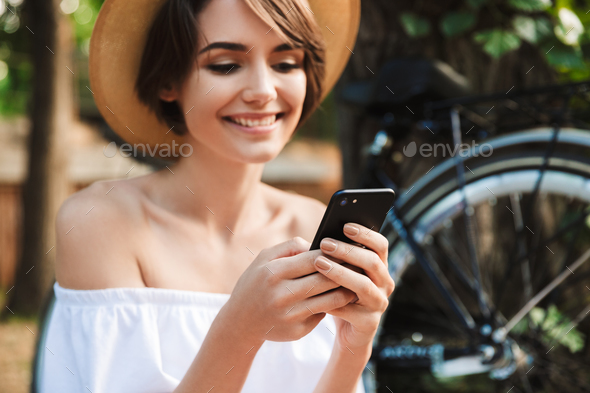Smiling young girl using mobile phone - Stock Photo - Images