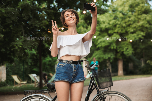 Smiling young girl taking a selfie while standing - Stock Photo - Images