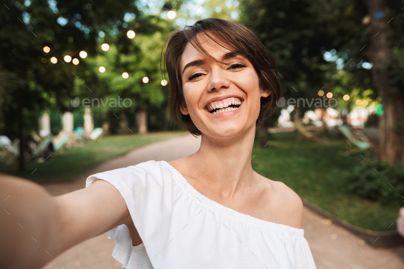 Smiling young girl taking a selfie - Stock Photo - Images