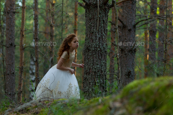 Little girl walks in a summer forest in a dress - Stock Photo - Images