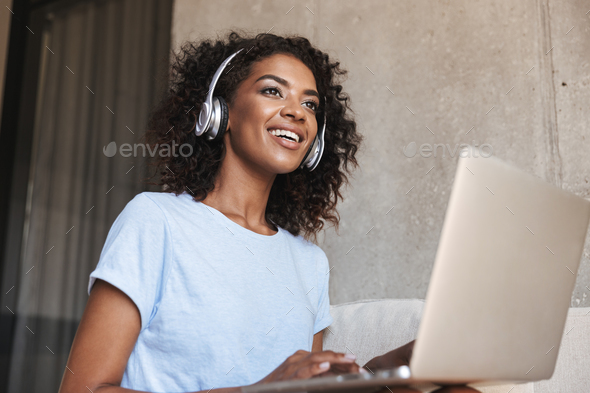 Smiling african woman in headphones - Stock Photo - Images