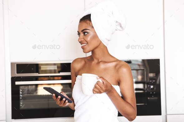 Happy african woman wrapped in a towel - Stock Photo - Images