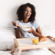 Laughing young african woman having tasty breakfast - PhotoDune Item for Sale