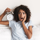 Confused young african woman showing alarm clock - PhotoDune Item for Sale