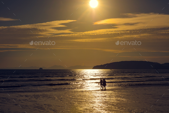 Friends Walking On Shore At Beach During Sunset - Stock Photo - Images