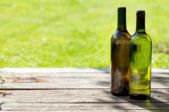 White wine bottles on wooden table - Stock Photo - Images
