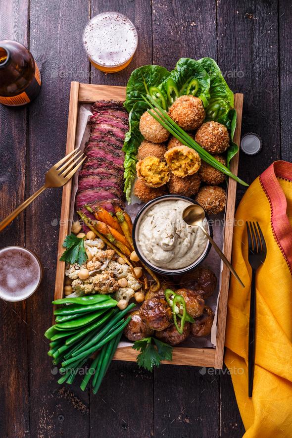 Meze dishes on a dark background. Meat, falafel, baba ghanoush, vegetables. Halal food. Copyspace - Stock Photo - Images