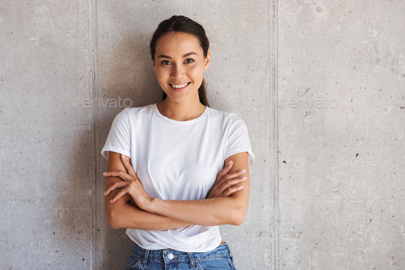 Smiling young asian woman standing with arms folded - Stock Photo - Images