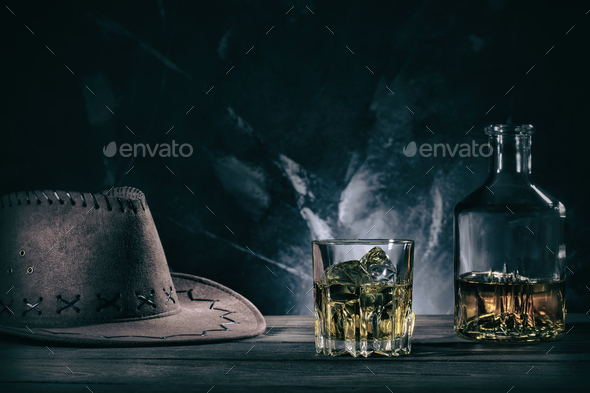 Glass of whiske and decanter with cowboy hat - Stock Photo - Images