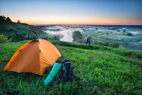 Orange tent and backpack on hill with tourist - Stock Photo - Images