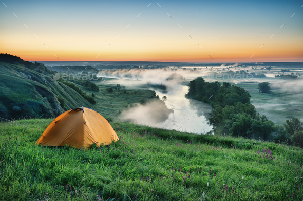 Orange tourist tent on hillside - Stock Photo - Images