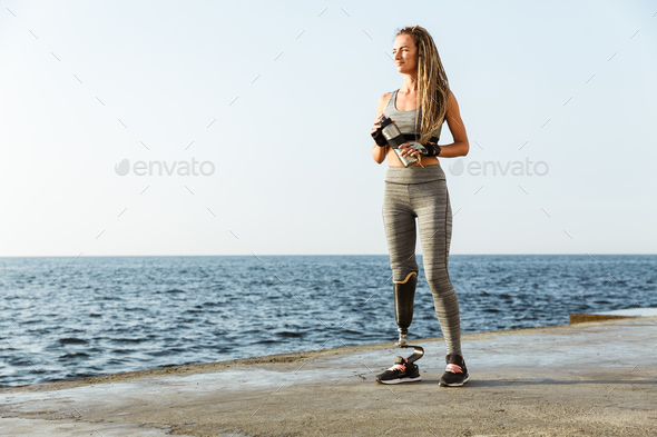 Full length of smiling disabled athlete woman - Stock Photo - Images