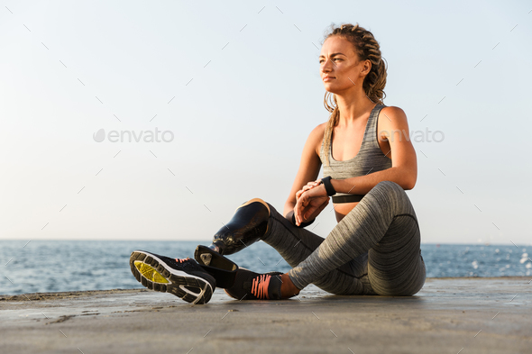 Smiling disabled athlete woman with prosthetic leg - Stock Photo - Images