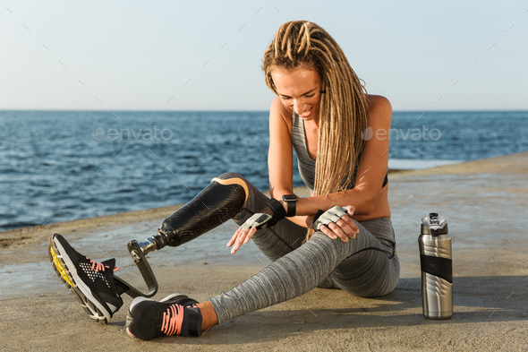 Laughing disabled athlete woman with prosthetic leg - Stock Photo - Images
