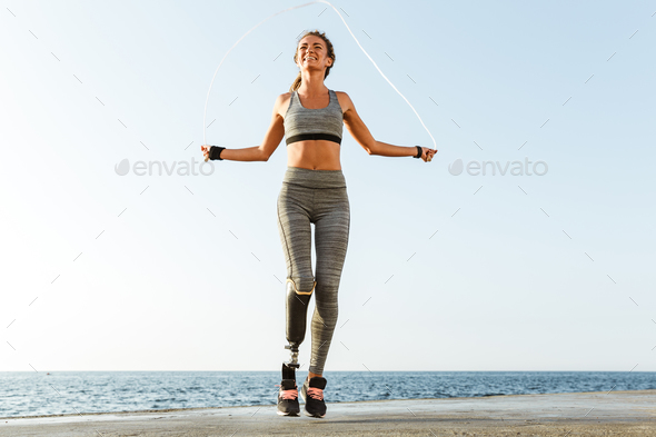 Disabled sports woman jumping with skipping rope - Stock Photo - Images