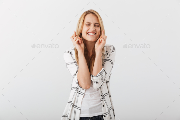 Portrait of an excited young casual girl holding fingers crossed - Stock Photo - Images