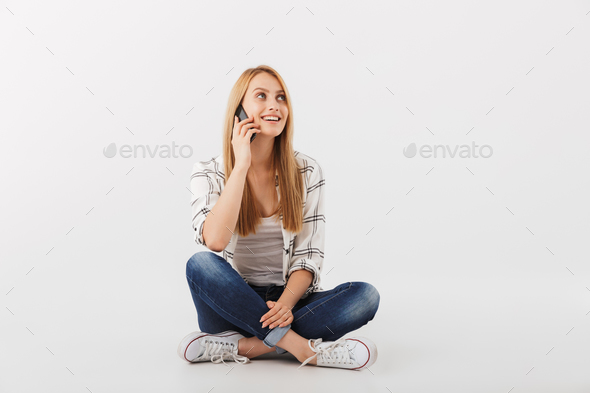 Portrait of happy young casual girl talking on mobile phone - Stock Photo - Images