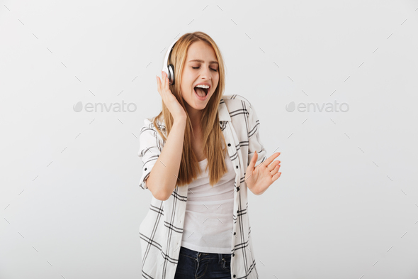 Happy young casual girl listening to music with headphones - Stock Photo - Images
