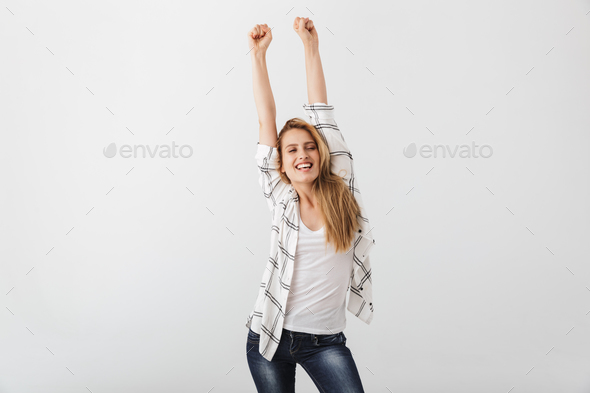 Portrait of an excited young casual girl celebrating success - Stock Photo - Images