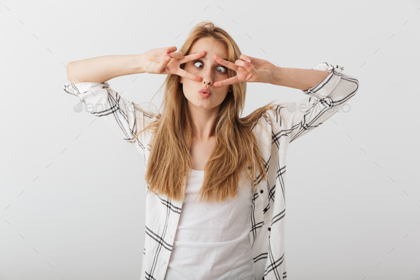 Portrait of a funny young casual girl showing peace gesture - Stock Photo - Images