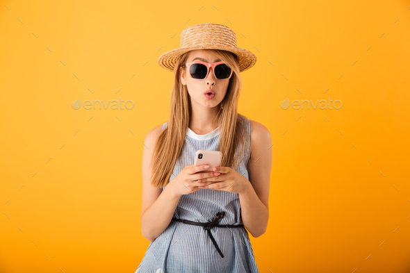 Portrait of a surprised young blonde woman in summer hat - Stock Photo - Images