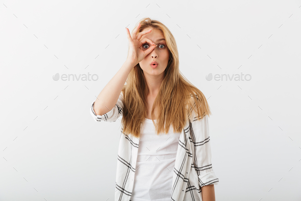 Portrait of a cheerful young casual girl showing ok - Stock Photo - Images