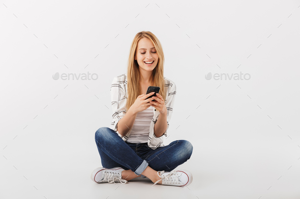 Portrait of angry young casual girl using mobile phone - Stock Photo - Images
