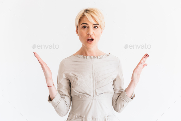 Portrait of excited mature blond woman 40s lifting arms with sur - Stock Photo - Images
