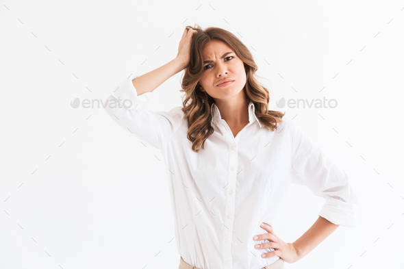 Portrait of puzzled young woman with long brown hair touching he - Stock Photo - Images