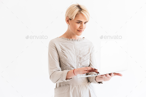 Elegant middle aged woman with short blond hair wearing dress ho - Stock Photo - Images