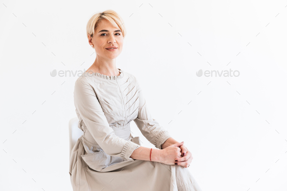 Portrait of pretty mature woman with short blond hair wearing dr - Stock Photo - Images