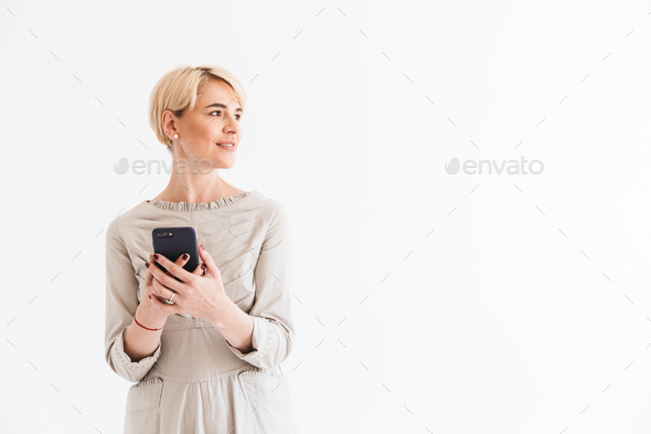 Smiling middle aged woman with short blond hair wearing dress ho - Stock Photo - Images