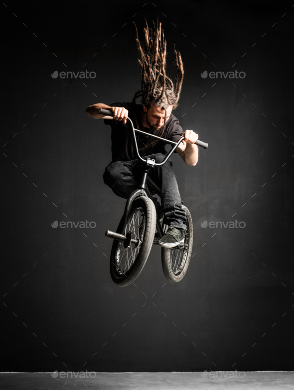 Young man with dreadlocks jumping on his BMX bike. - Stock Photo - Images