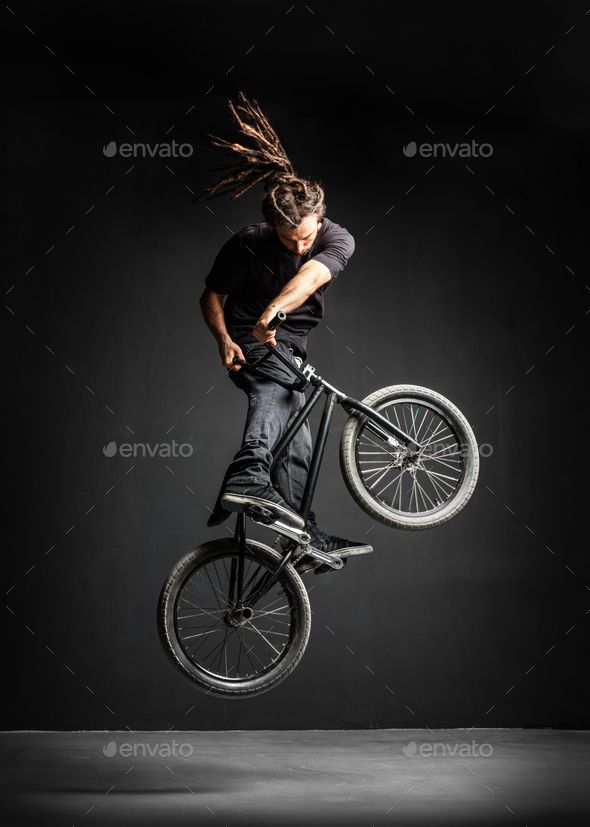 A man doing an extreme stunt on his BMX bicycle. - Stock Photo - Images
