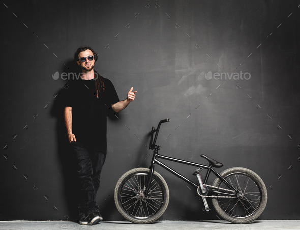 Man standing next to his BMX bike, pointing his finger. - Stock Photo - Images