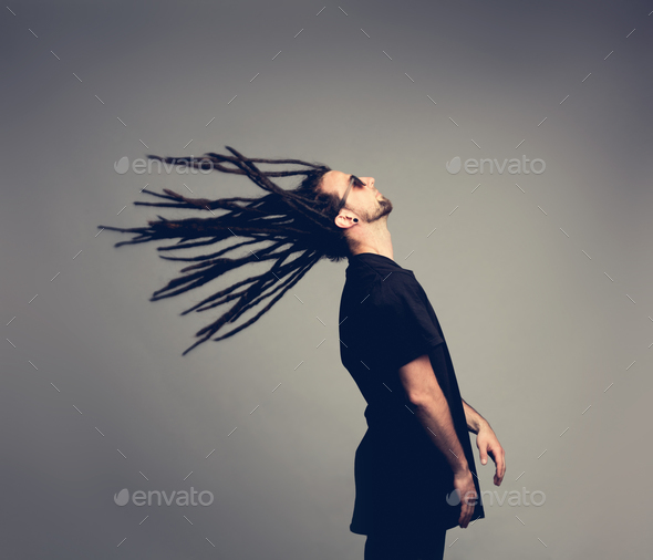 Young man flipping his dreadlocks back. - Stock Photo - Images