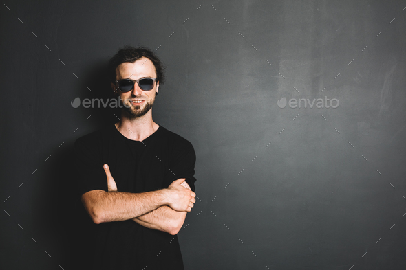 Portrait of smiling casual man standing on grunge wall. - Stock Photo - Images